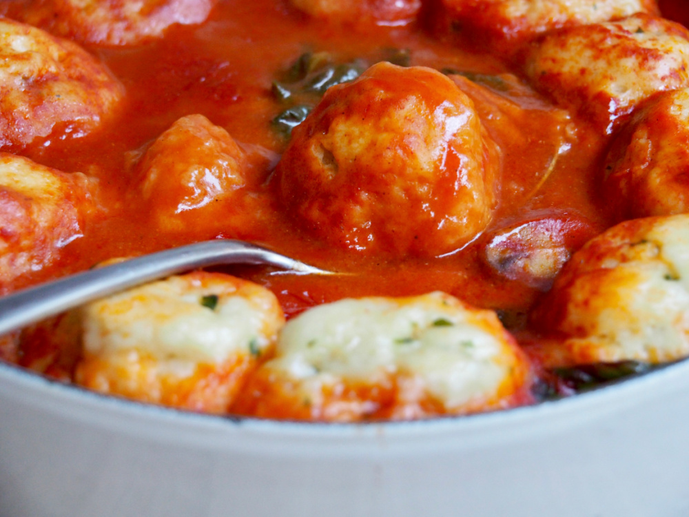 dumpling on serving spoon in pot of chicken and paprika stew