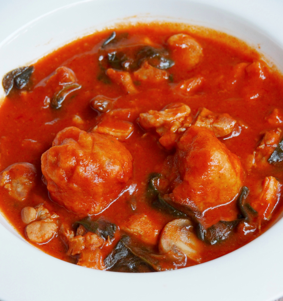 side plate of pot of paprika chicken stew with chive dumplings