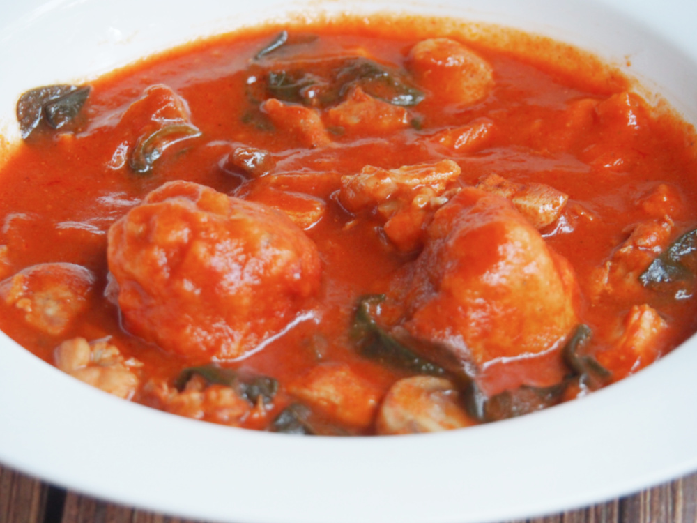 plate of paprika chicken stew with chive dumplings