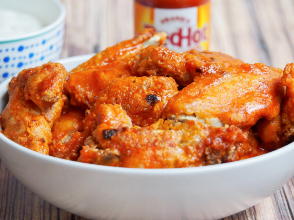 bowl of oven baked chicken wings with Franks hot sauce in the background