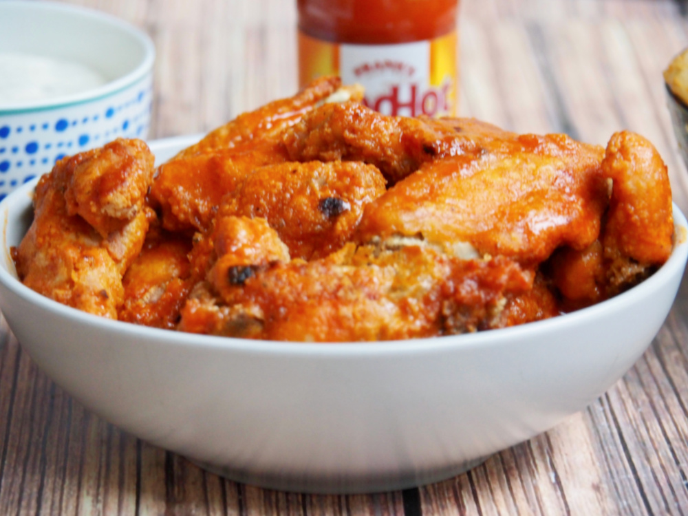 oven baked chicken wings in bowl with Frank's hot sauce in background