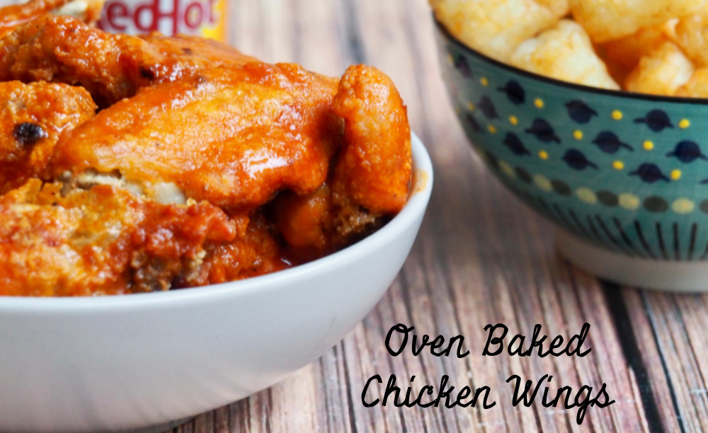 side view of oven baked chicken wings with bowl of tater tots in background