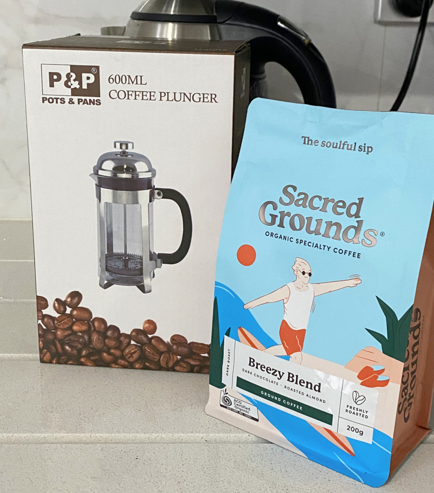 coffee plunger and packet of sacred grounds coffee