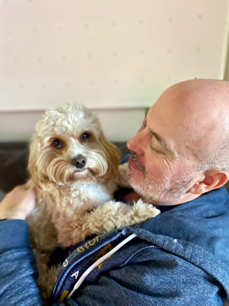 man lying on sofa and cuddling a cavoodle