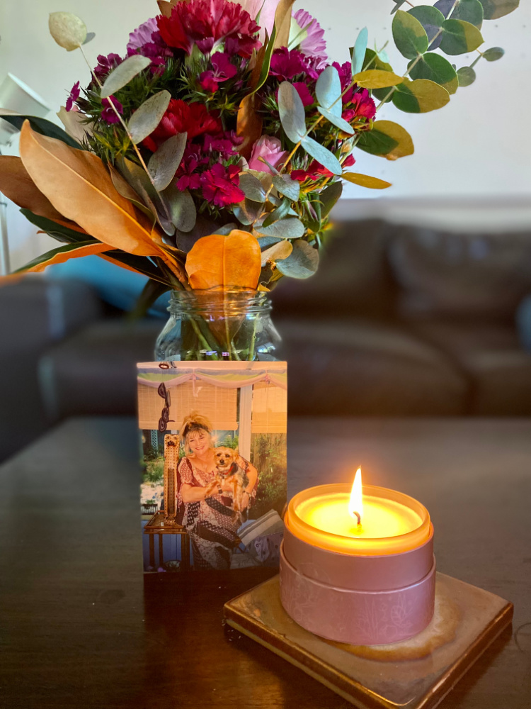 picture of woman holding a dog next to a candle and flowers
