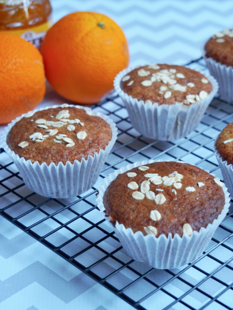 marmalade muffins on cooling rack with oranges in background
