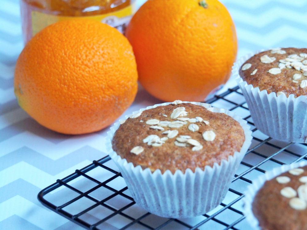marmalade muffin on cooling rack with oranges and jar of marmalade in background