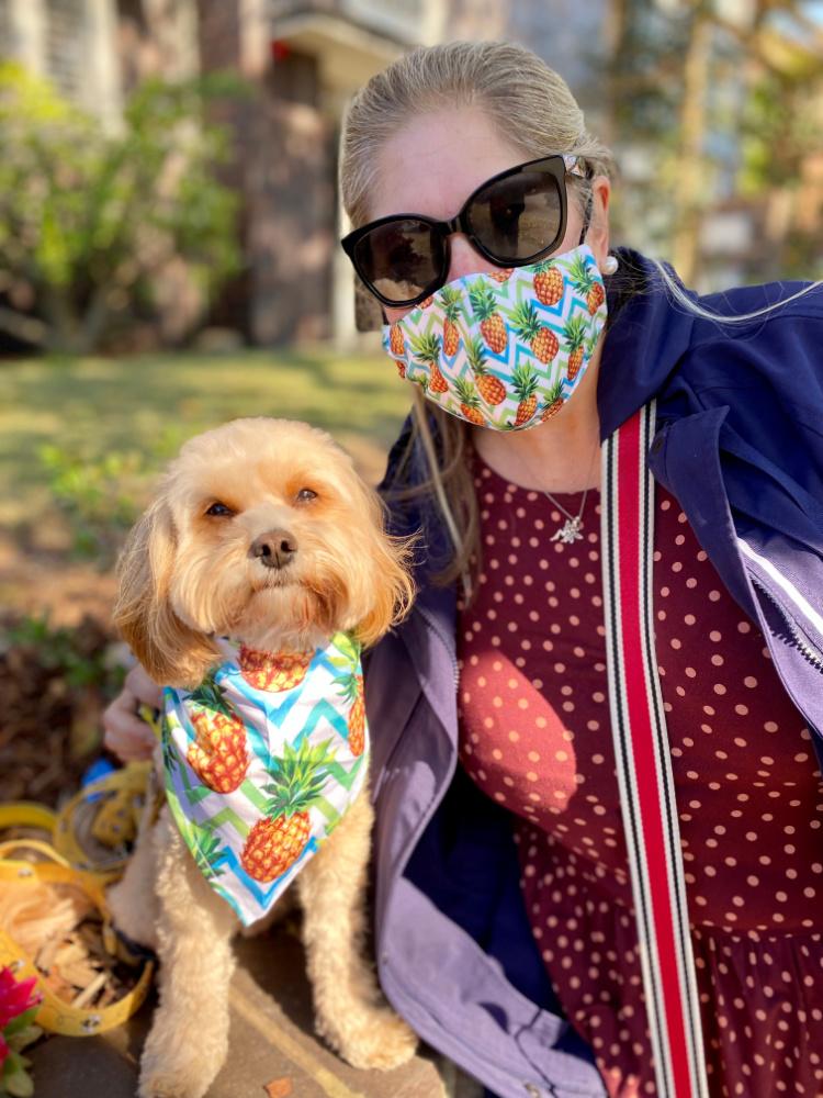 woman and dog wearing matching pineapple mask and bandana