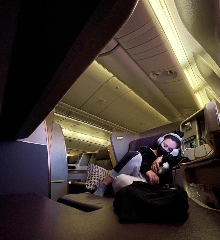 woman sleeping under blanket in business class