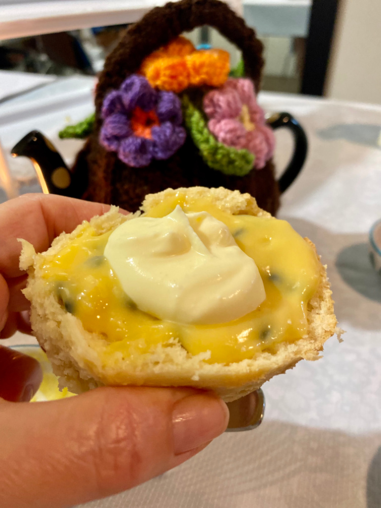 hand holding scone with passionfruit curd and cream and teapot with tea cosy in background