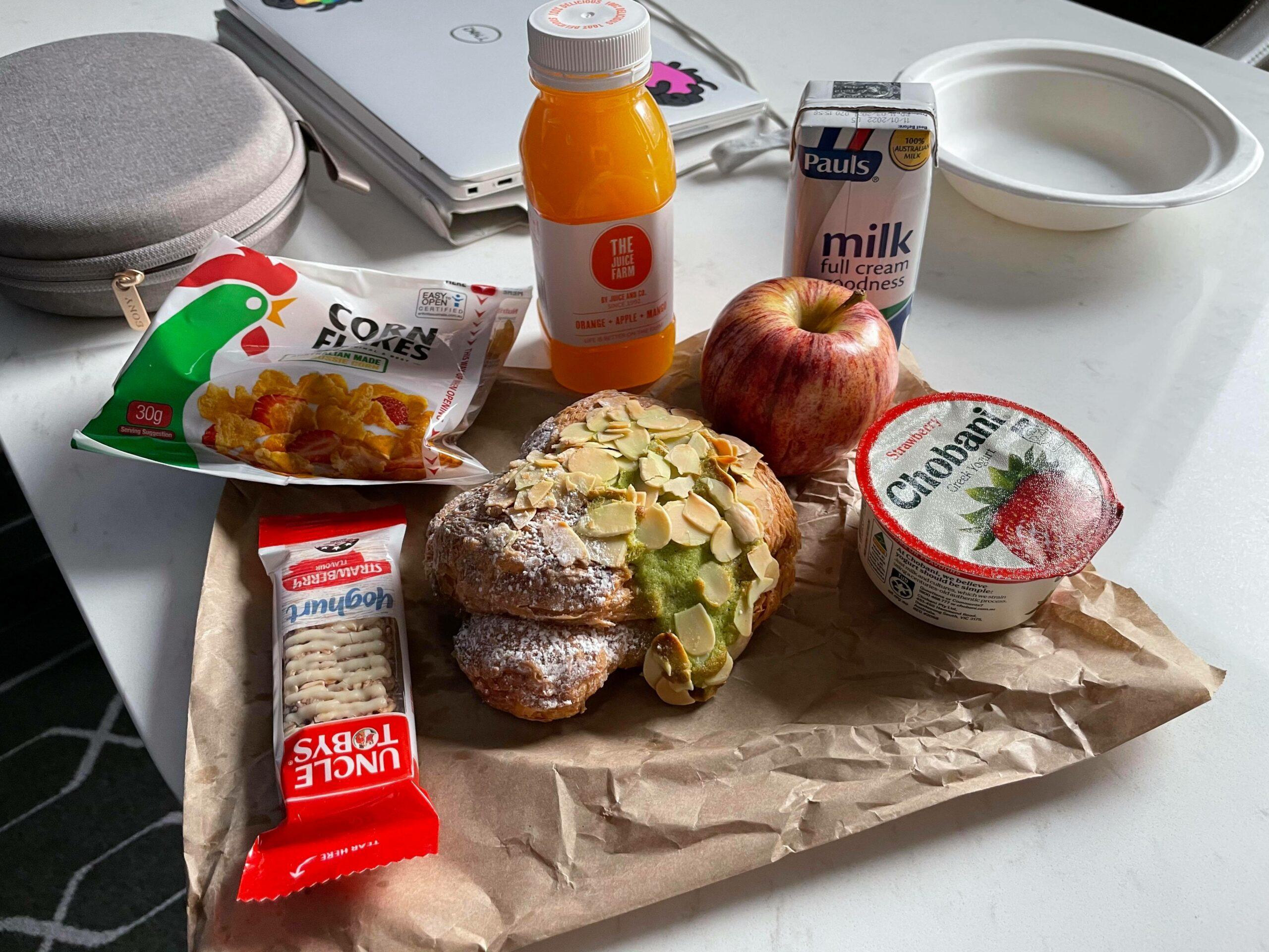 almond croissant yoghurt juice laid out on brown paper bag