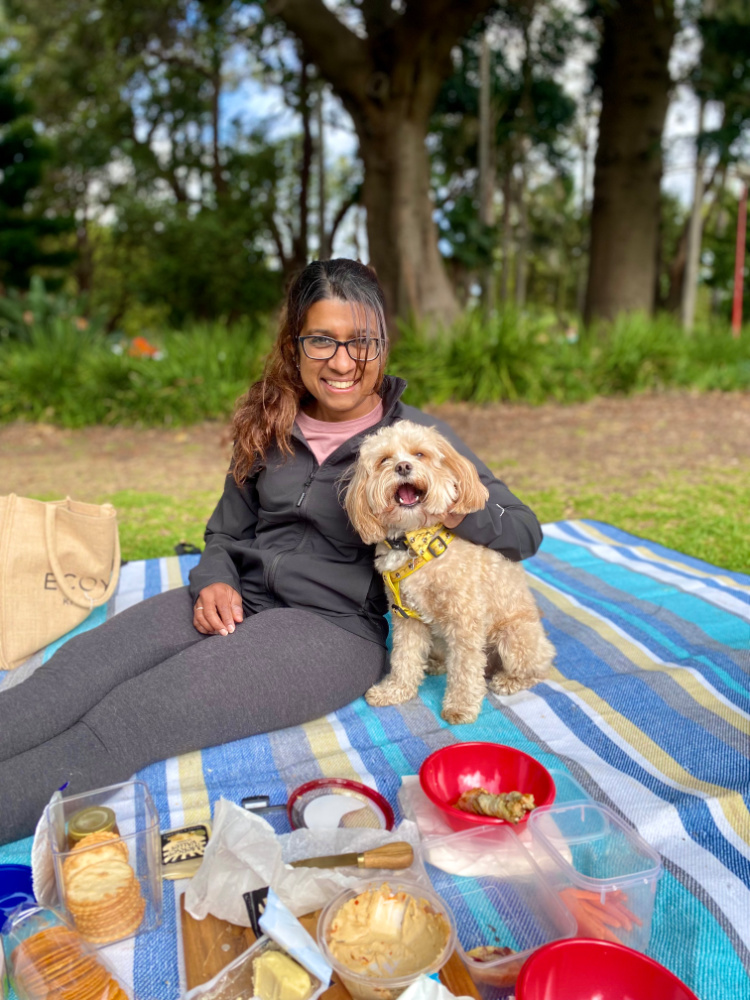 woman sitting on a picnic blanket cuddling a cavoodle