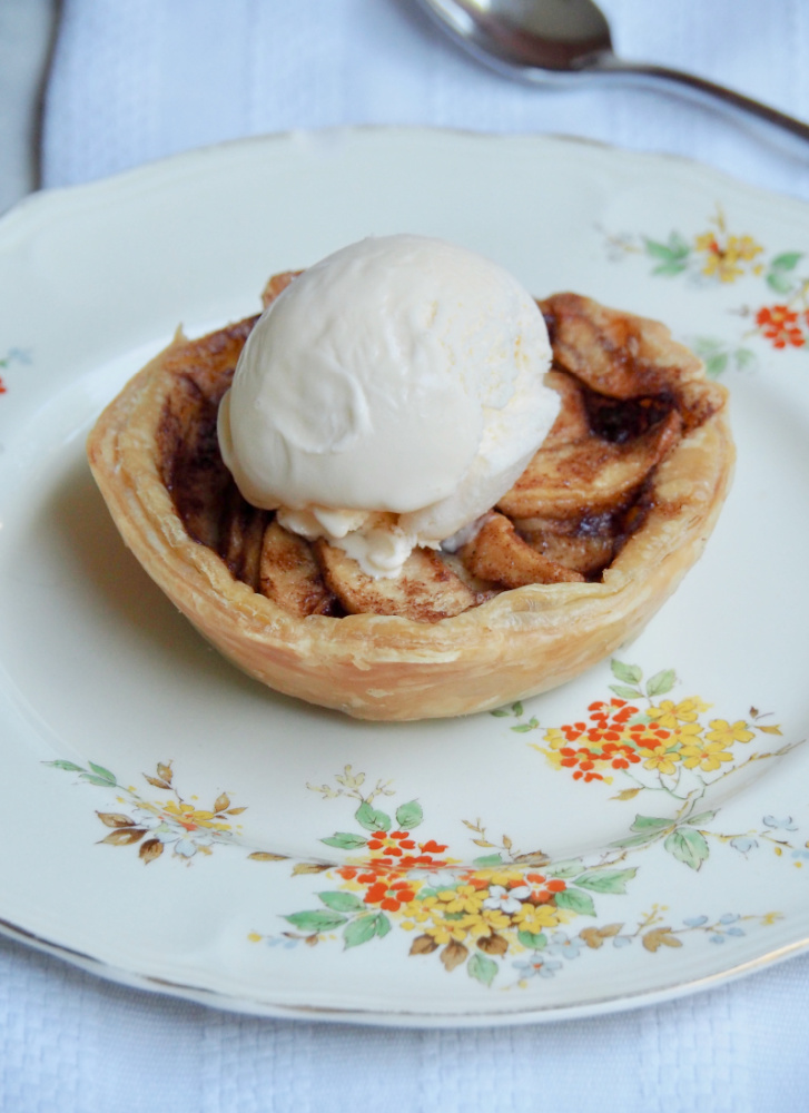 individual open topped apple pie with scoop of ice cream on top