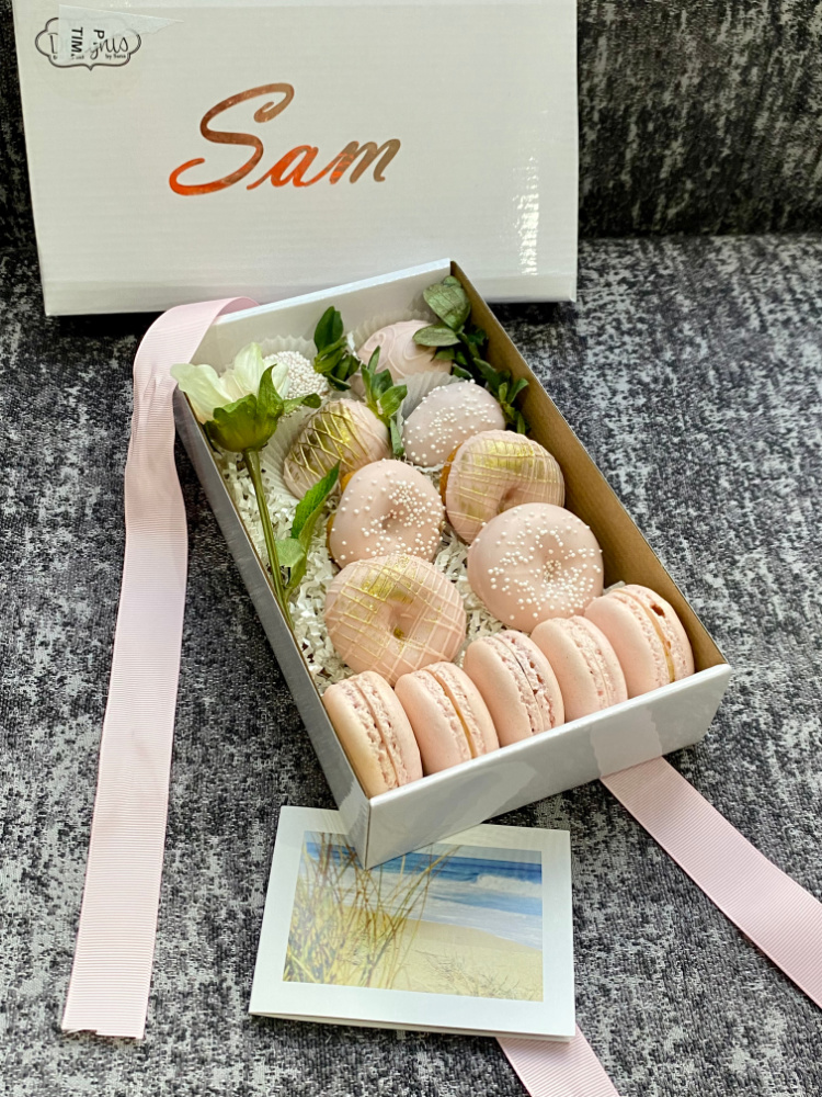 box of pastel pink donuts and macarons
