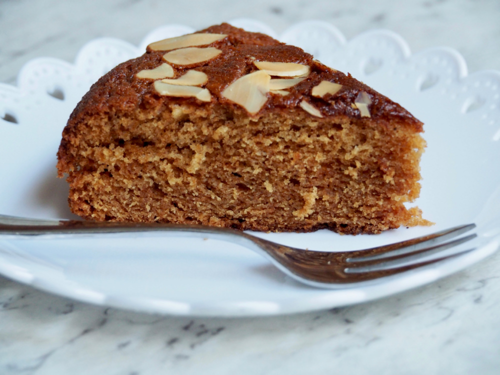slice of honey cake on white plate with small cake fork
