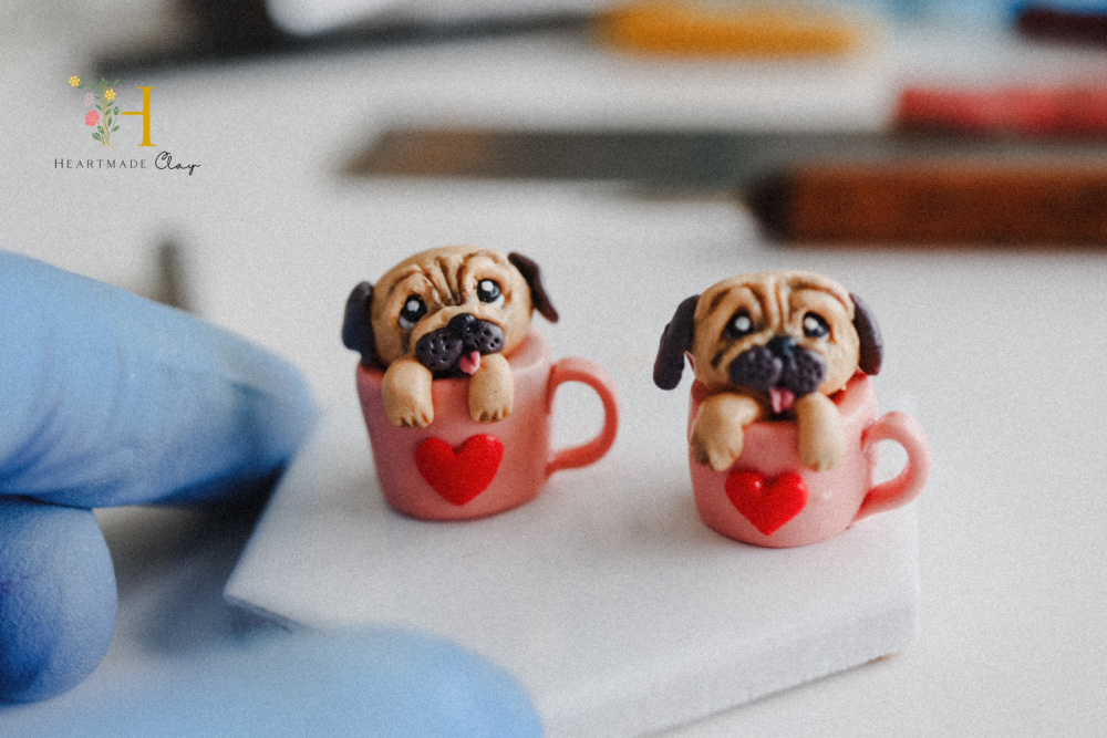 small polymer sculptures of pugs in mugs