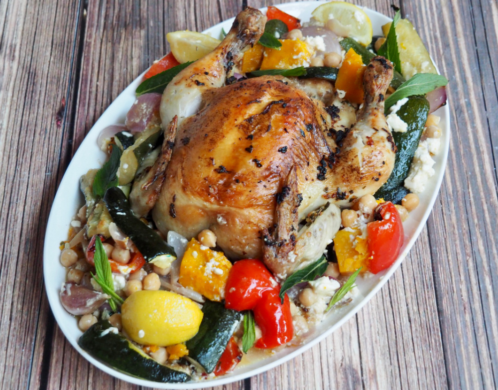 looking down on roast chicken with peppers pumpkin and feta