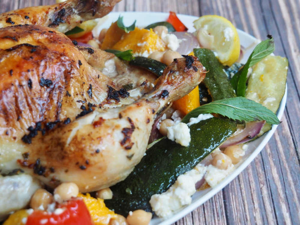 partial close up of roast chicken on white platter with peppers and pumpkin