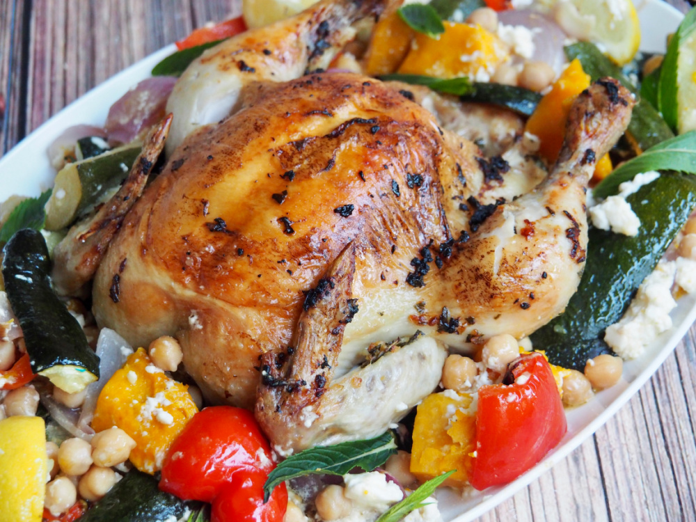 close up of roast chicken surrounded by peppers and pumpkin on white platter