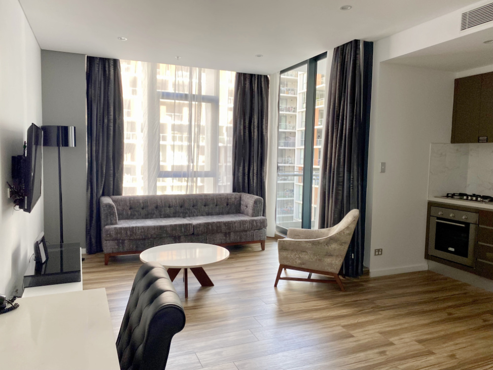 serviced apartment llving room with sofa chair and desk
