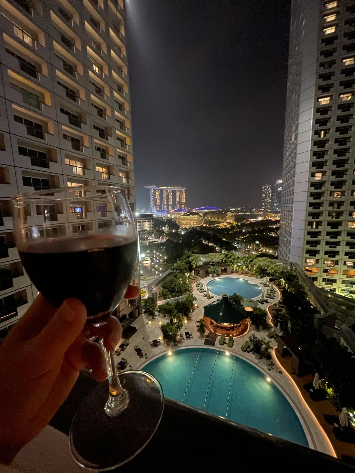 hand holding a glass of wine on balcony overlooking a hotel pool at night