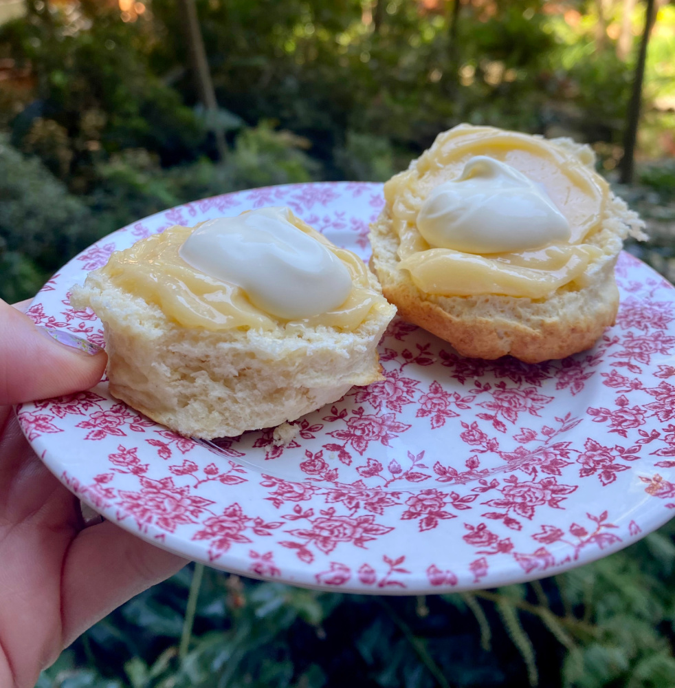 scone cut in half spread with lemon butter and cream